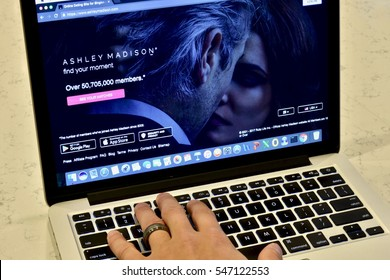 WASHINGTON DC, USA - JANUARY 02, 2017: An Apple Macbook Pro displaying the Ashley Madison hook-up website while a married man appears to be browsing it.