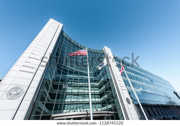 Washington DC, USA - January 13, 2018: US United States Securities and Exchange Commission SEC entrance architecture modern building sign, entrance, american flag, looking up sky, glass windows