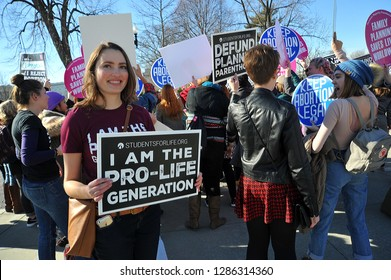 Washington, D.C. / USA - January 19, 2018: A young woman holds a pro-life sign near the US Supreme Court during the March For Life, the largest pro-life march in the world.