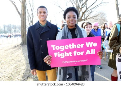 Washington DC / USA; January 20, 2018: Jeremy Woods and Nelsy Assoum march during the 2018 Women's March on Washington DC. Their sign says 'Together We Fight For All Planned Parenthood'.