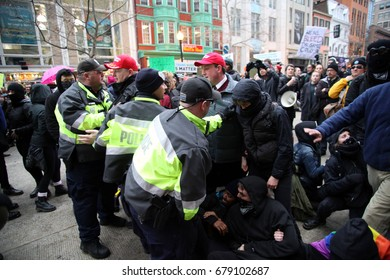 Washington, D.C., USA - January 20, 2017:  Police assist two men trying to get past anti-Donald Trump protesters blocking access to a checkpoint to enter the area of authorized inaugural activities.