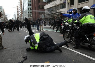 Washington, D.C., USA - January 20, 2017:  A police officer sprays pepper spray at anti-fascist, anti-Donald Trump protesters as a colleague tries to get to his feet during an Inauguration Day march.