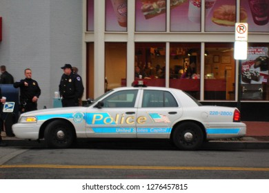 Washington, DC / USA - January 2010: Police car and two police officers in front of a Dunkin' Donuts store in downtown Washington DC