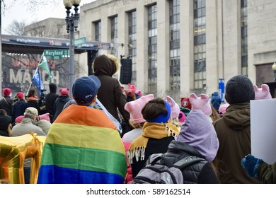Washington D.C., USA January 21, 2017- Women's March on Washington: Protesters gather at the rally stage in massive crowd, a protester wearing a Gay Pride, rainbow flag around his body is featured.