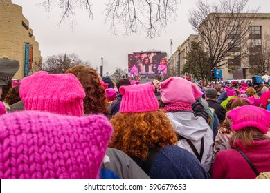 WASHINGTON, DC, USA – JANUARY 21, 2017: Close-up of pink hats worn by protesters listening to speeches at the Women's March in Washington, DC. On the screen is Senator Kamala Harris of California.