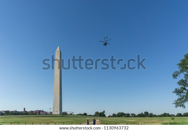 Washington, DC / USA - July 10, 2018: President Trump departs the White House and flies past the Washington Monument on his helicopter, Marine One, as he heads to a week of meetings in Europe.