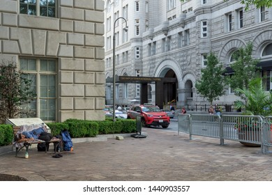 Washington, DC / USA - July 2, 2019: A homeless man sleeps on a bench next to the Trump International Hotel in downtown Washington, DC, the day President Trump declared that he cured homelessness.