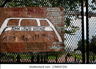 Washington, DC, USA - July 25, 2020: Protest art in tribute to Congressman John Lewis, hero of the civil rights movement, hangs on the fence at Lafayette Square with the White House in the background