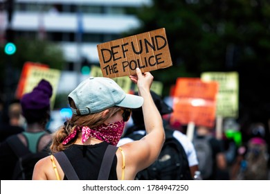 """Washington, DC, USA - July 25, 2020: A protester carries a sign that says """"Defund the Police,"""" during the March Against Trump's Police State, sponsored by the Party for Socialism and Liberation"""