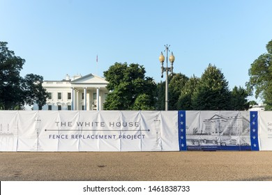 """Washington, DC / USA - July 26, 2019: As part of the White House fence replacement, a privacy barrier has been erected.  The picture on it is mislabeled South Lawn"""" of the White House; it's the front."""