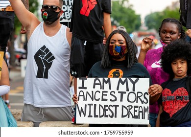 """Washington, DC, USA - June 19, 2020: A young protester and celebrant of Juneteenth holds a sign that reads """"I am my ancestors' wildest dream"""" at Black Lives Matter Plaza / Lafayette Square"""