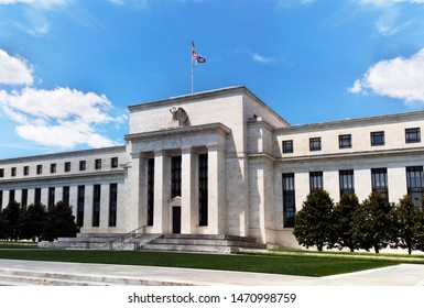 Washington DC, USA - June 22, 2019: Exterior view of Federal Reserve Board of Governors Building facade entrance with eagle stone statue and American flags over a blue cloudscape sky.