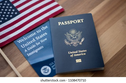 Washington, DC, USA - June, 5, 2018: Passport of USA (United states of America) next to a Guide for new Immigrants - Welcome to the United states and American Flag. Wooden Background.