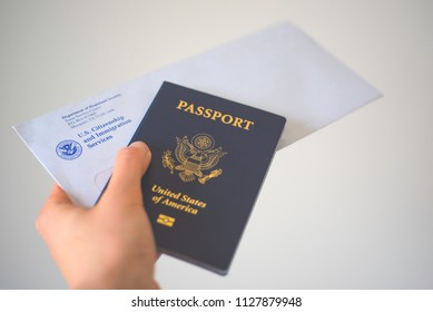 Washington, DC, USA - June, 5, 2018: Envelope from USCIS (United states citizenship and immigration Services) and Passport of USA in Hand, blurred toned on  white background.