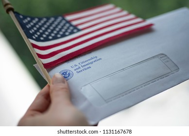Washington, DC, USA - June, 5, 2018: Envelope from USCIS (United states citizenship and immigration Services) and Flag of USA in left Hand, blurred toned on green and white background.