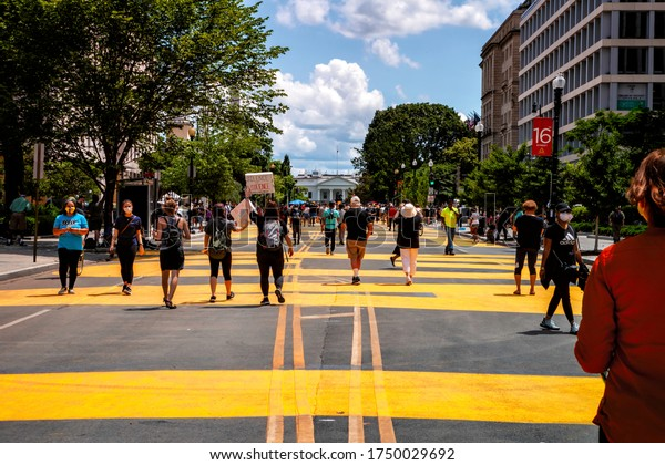 Washington, DC, USA - June 5 2020: Protesters examine the new mural at Black Lives Matter Plaza in front of the White House and Lafayette Park