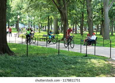 Washington, D.C, USA - June 6,2018 ; A group of tourists riding the bicycles on the pathway in the park of National Mall in DC.