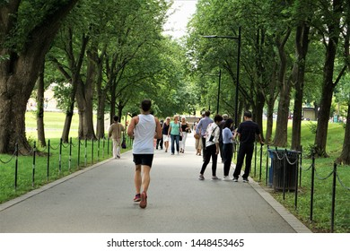 Washington, D.C, USA - June 6,2018 ; A man was running for exercise on the pathway in the park of National Mall in Washington, D.C and the group of the tourists walking.