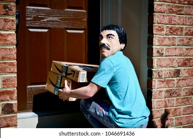 WASHINGTON DC, USA - MARCH 15, 2018: Concept of a man in a mask stealing Amazon Prime packages from the front door of a home.