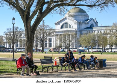 WASHINGTON DC, USA - March 27, 2019: People relaxing in the  National Mall in front of Smithsonian National Museum of Natural History during spring. Several museum are located near the National mall.