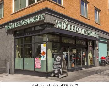 WASHINGTON, DC, USA - MARCH 30, 2016: People on sidewalk pass Whole Foods Market in Foggy Bottom neighborhood.