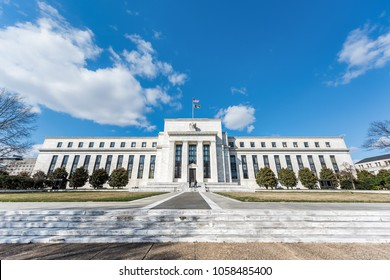 Washington DC, USA - March 9, 2018: Federal Reserve bank entrance wide angle architecture building wall security guard doors, path, american flags, blue sky