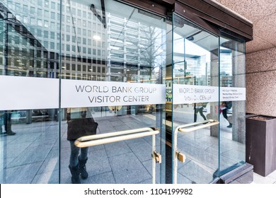 Washington DC, USA - March 9, 2018: World Bank Group Vistor Center with gift shop to public sign doors in winter, window, entrance to building, people pedestrians walking on street sidewalk reflection