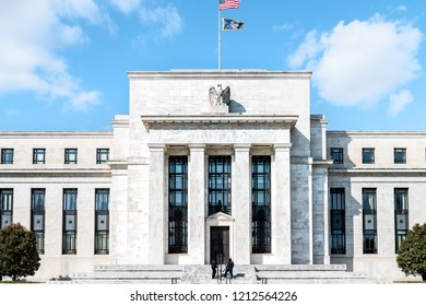 Washington DC, USA - March 9, 2018: Federal Reserve bank entrance, facade architecture building, wall security guards standing by doors, path, American flags, blue sky