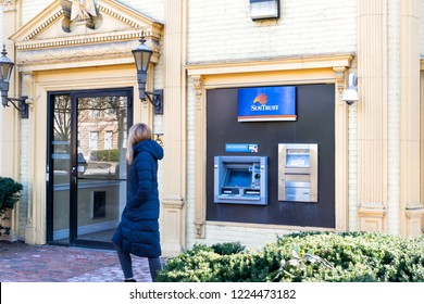 Washington DC, USA - March 9, 2018: Suntrust bank, banking branch, office building entrance at Dupont Circle, people, woman walking, ATM, depository slot, door