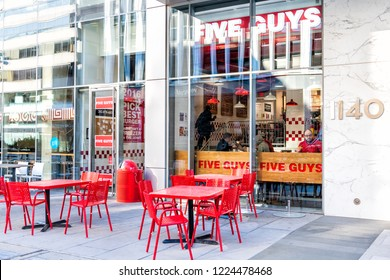 Washington DC, USA - March 9, 2018: Five Guys restaurant, store burger chain entrance in District of Columbia with chairs, tables, outside, outdoor sitting area, people inside eating