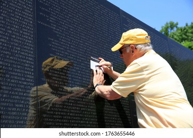 Washington DC, USA - May 02, 2019: Volunteer take a rubbing of a Name at the Vietnam War Memorial on the Mall in Washington DC. The Names are in chronological order. USA