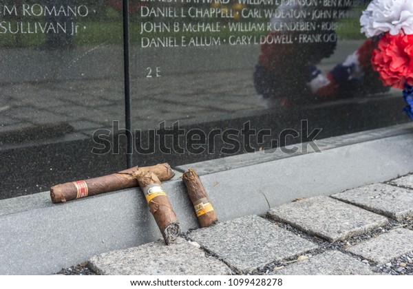 """Washington, DC / USA - May 27, 2018: On Memorial Day, friends honor their fallen colleagues at the Vietnam Veterans Memorial, also called """"The Wall."""""""