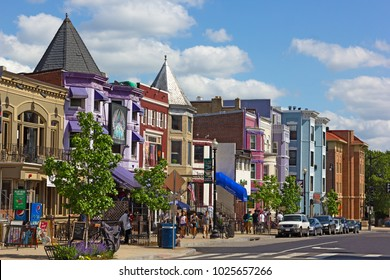 WASHINGTON DC, USA -  MAY 9, 2015: Row houses and businesses in Adams Morgan neighborhood on a perfect spring day with young people walking on the street.