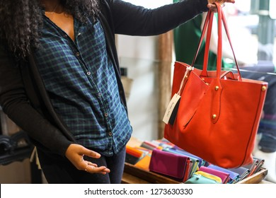 Washington, DC / USA - November 2, 2018: A young woman wearing a plaid shirt shops in a local boutique in Georgetown and examines a red handbag.