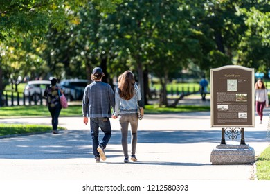 Washington DC, USA - October 12, 2018: Back of young couple walking in Capitol Square park holding hands during sunny autumn day by US Congress on capitol hill