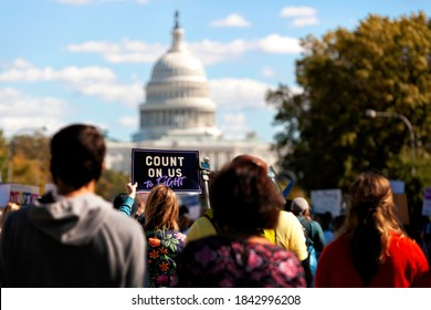 """Washington, DC, USA - October 17, 2020: A protester carries a Women's March sign that says """"Count On Us,"""" while walking down Pennsylvania Avenue toward the U.S. Capitol"""