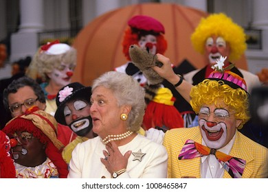 Washington, DC. USA, October, 1989 First Lady Barbara Bush clowning around with clowns on the South Lawn of the White House during Halloween event