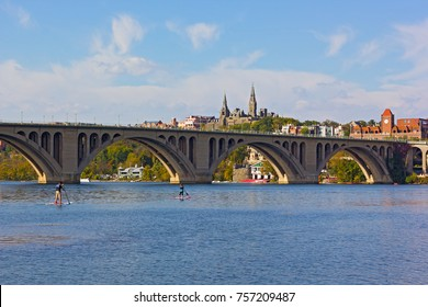 WASHINGTON DC, USA -?? OCTOBER 30 2016: Young couple kayaking on Potomac River near Key Bridge on a sunny afternoon. Unseasonably warm weekend is a perfect time for water activities.