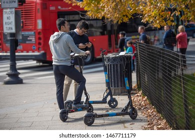 Washington, DC, USA - October, 31, 2018: Two men choosing electric scooter for city ride. Red city bus on a background.  Autumn fall season.