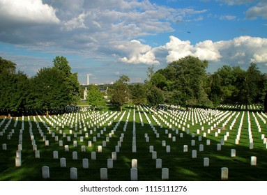 Washington D.C., USA - September 15, 2017: Arlington National Cemetery - perspective of tombstones on summer day. In the background you can see distant Washington D.C. Skyline.
