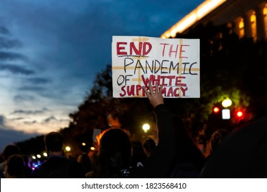 """Washington, DC, USA - September 23, 2020: A protester at the March for Justice for Breonna Taylor holds a sign that says, """"End the pandemic of white supremacy"""""""