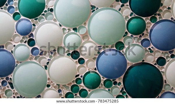 Washington, D.C. / U.S.A. - September 24, 2016: Hospital decorative bathroom wall with mosaic glass pieces and round, spherical, bubble-like tiles that are blue and green in a white mortar grout.