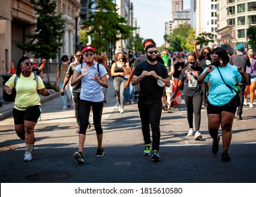 Washington, DC, USA - September 7, 2020: Four American Sign Language interpreters walking down 14th Street, signing as the crowd sings traditional songs during Let Freedom Sing