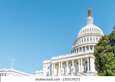 Washington DC, USA US Congress dome construction exterior with steps stairs view and flag on Capital capitol hill with blue sky columns pillars and scaffolding