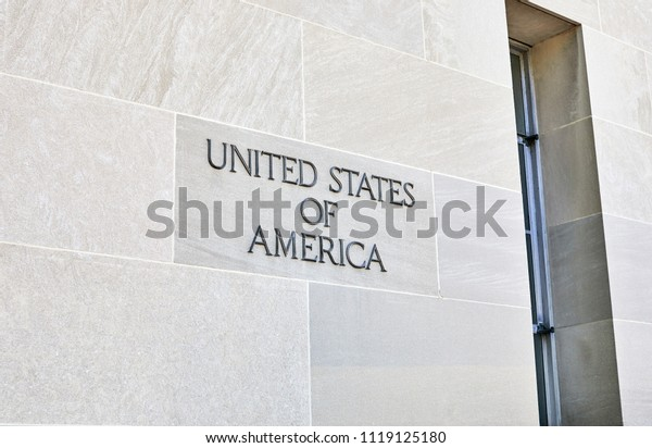 Washington DC, USA-June 5, 2018: Robert F Kennedy Department of Justice building sign on stone wall reading United States of America