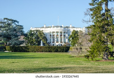 Washington DC, VA, USA - Dec 26th 2014: The White House Facade. House of the President of the United States. Green Garden with Lawn and Trees on a Sunny Day with Bright Blue Sky.