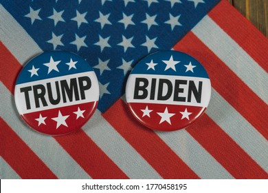 Washington DC--July 5, 2020; Red white and blue Donald Trump and Joe Biden Presidential campaign buttons, commonly worn by voters during election season, sit on an American flag on a wooden table.