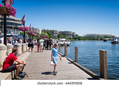 WASHINGTON DC-May 24, 2015: Georgetown waterfront dock, crowded with people who come for the restaurants, river cruises and other entertainment. Kennedy Center and Watergate complex in the background.