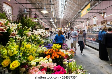 WASHINGTON DC-May 24, 2015: Inside the historic Eastern Market in the Capitol Hill neighborhood, first opened in 1805. Image of shoppers browsing. Colorful flower stand in the foreground.