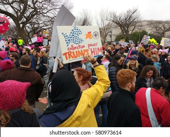 """Washington, D.C./USA January 21 2017: Women's March on Washington: Protesters gathered on the National Mall. A demonstrator holds a sign that says, """"Collective Power Trumps Him""""."""